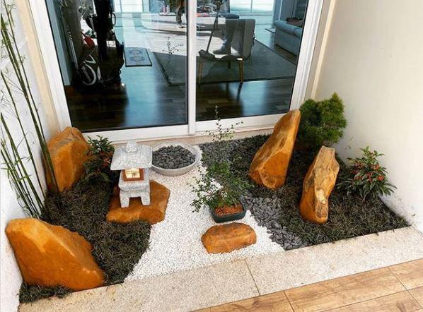 a small japanese style zen garden in a garden alcove