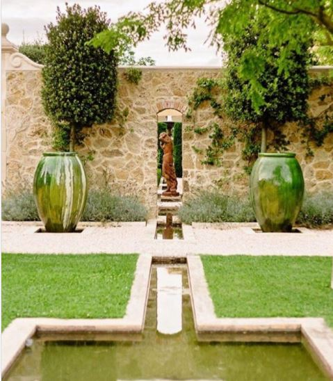two large green pots flank a bronze scultpture in a symmetrical italian style garden with pond