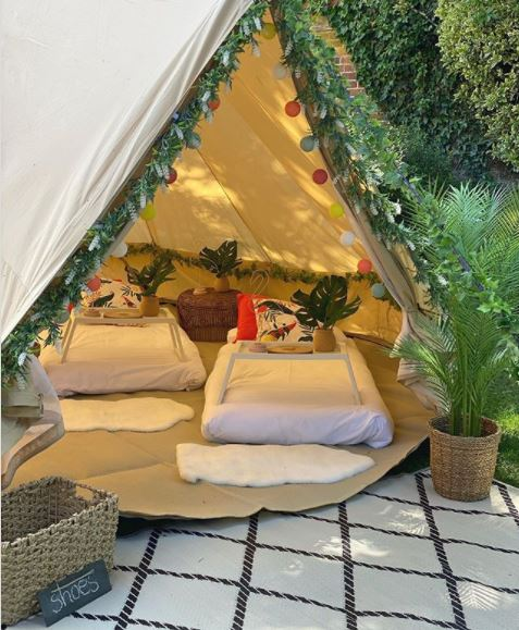 a peek inside a cosy bell tent with mattresses, rugs and artificial plant wreaths as decorations