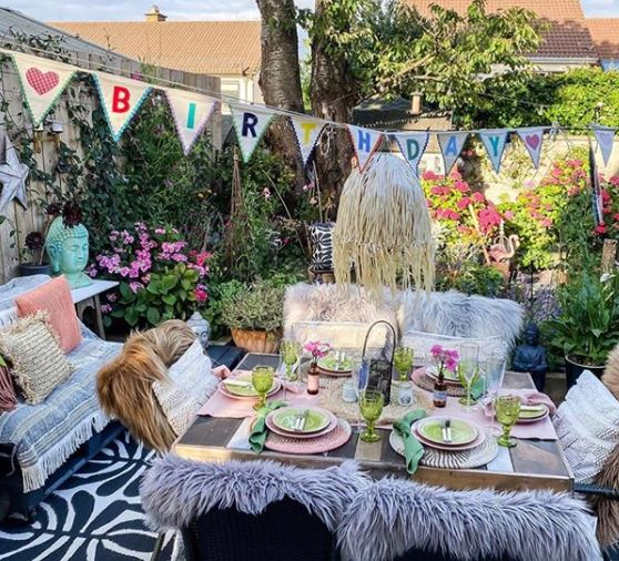 """cosy patio seating with rustic bunting that says """"happy birthday"""""""