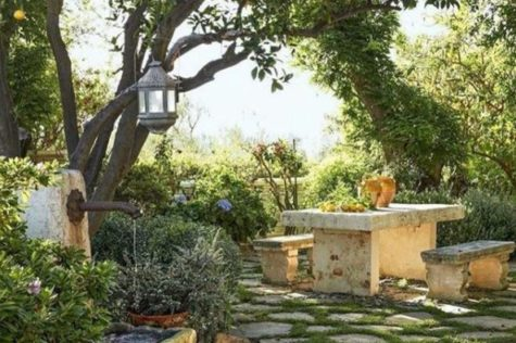Italian style garden ideas with mossy paving stones, stone bench, water fountain and orange trees