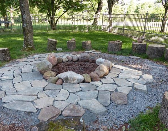a rustic stone fire pit with stone flooring surrounding it