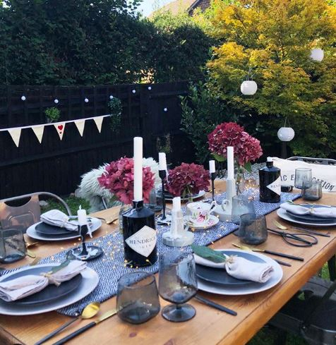 a wooden patio table with floral centrepieces and beautiful table settings