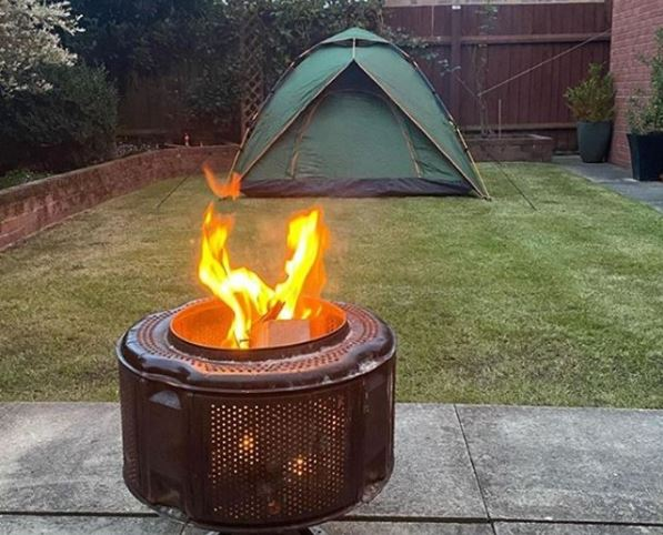 a modern green tent in a garden and a fire pit burning outside