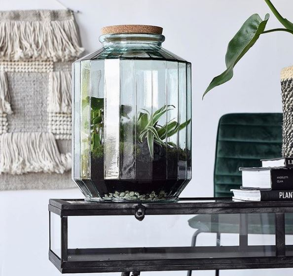 a large jar with angled edges filled with soil and plants