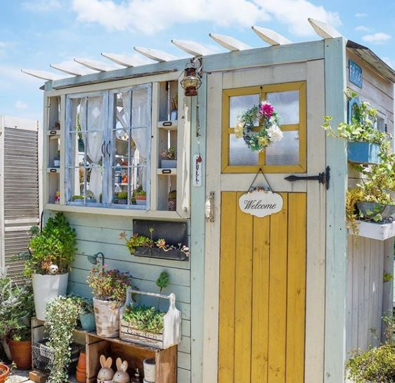 a pale blue beachy shed with a sunny yellow door