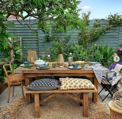 wooden patio furniture with cushions and table settings