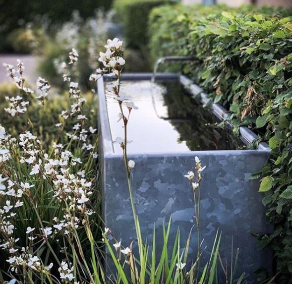 a metal trough nestled in a flower bed with a spout of water gently flowing into it