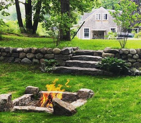 simple stone fire pit dug into grass
