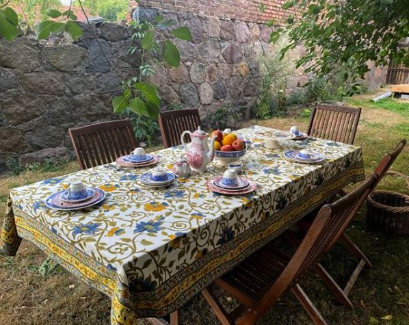a cosy outdoor table with a floral, bohemian tablecloth