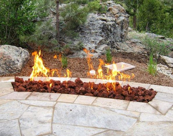 a gas powered fire pit coming out of a patio floor
