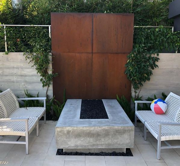 a sculptural fire pit with rust coloured metal backdrop