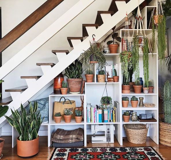 under stair shelves filled with books and plants