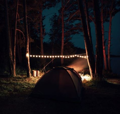 two tents at night, with a bright string of lantern lights between them