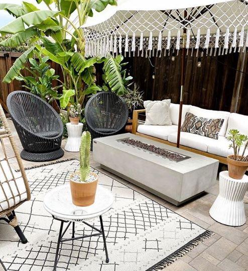 a concrete fire pit table on a stylish monochrome patio