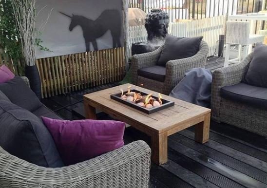 a wooden coffee table with shallow black fire pit feature