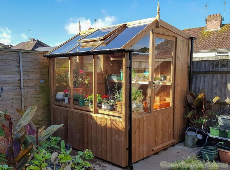 a potting shed with windows along one side filled with plants