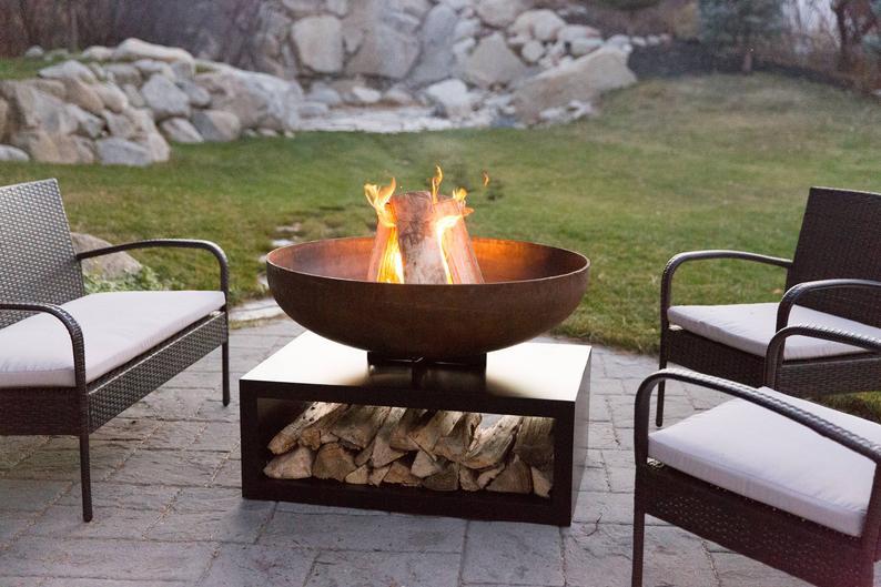 a metal garden fire bowl with log storage underneath