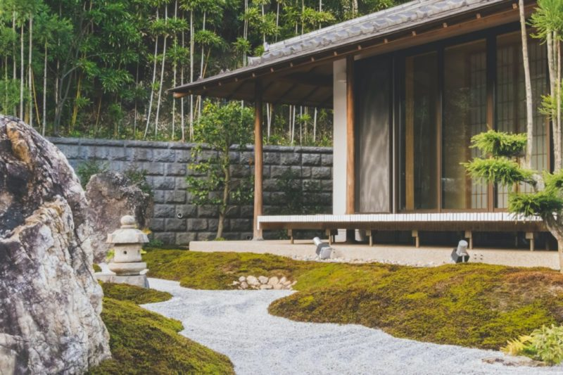 """A Japanese building with a mossy garden and pebble """"stream"""""""