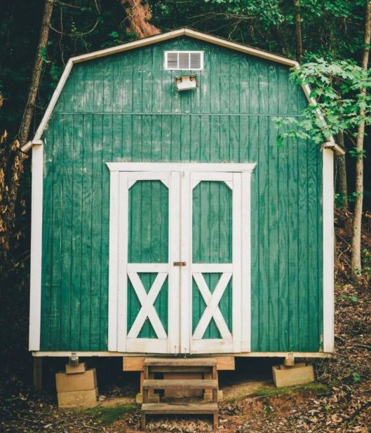 an american barn style shed painted green