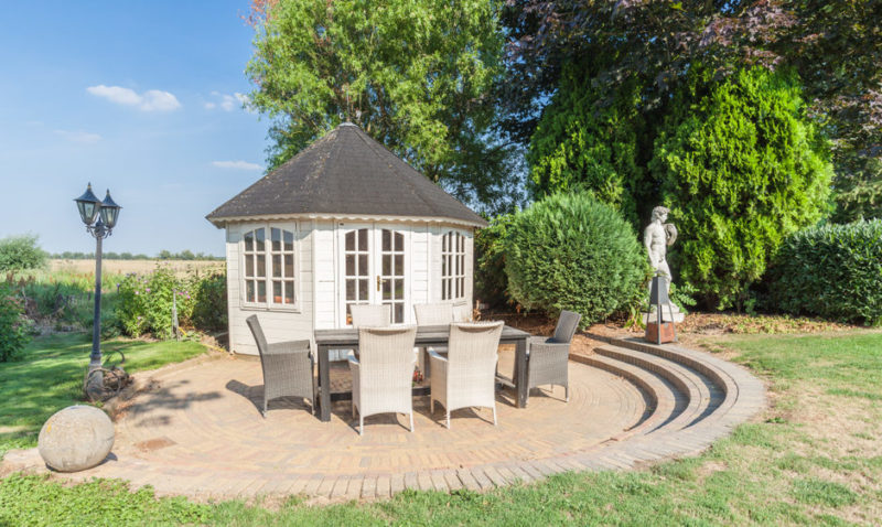 an octagonal pavilion style shed with garden furniture outside