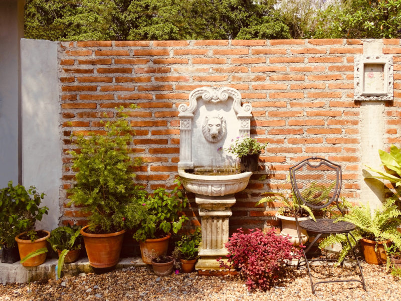 a wall-mounted stone fountain in the shape of a lion
