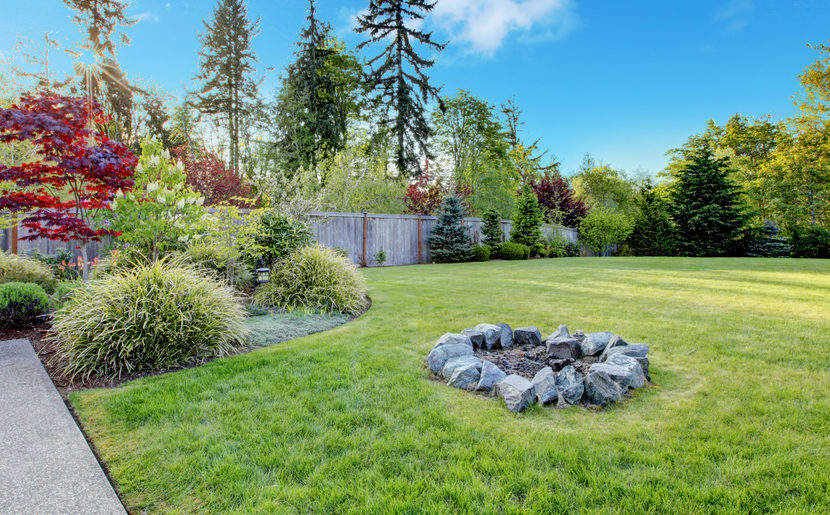 a ring of stones with a campfire in the middle of a lawn