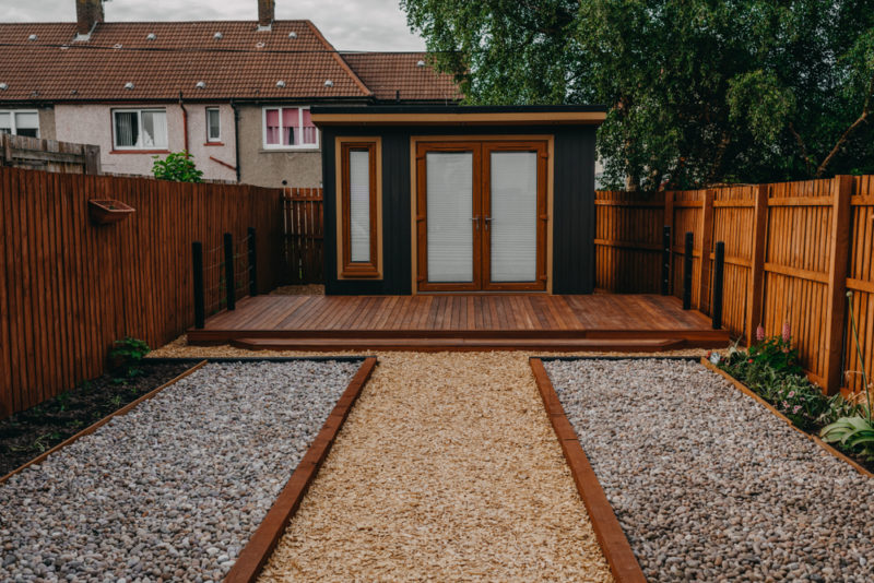 a minimalist shed painted black and brown in a gravel garden