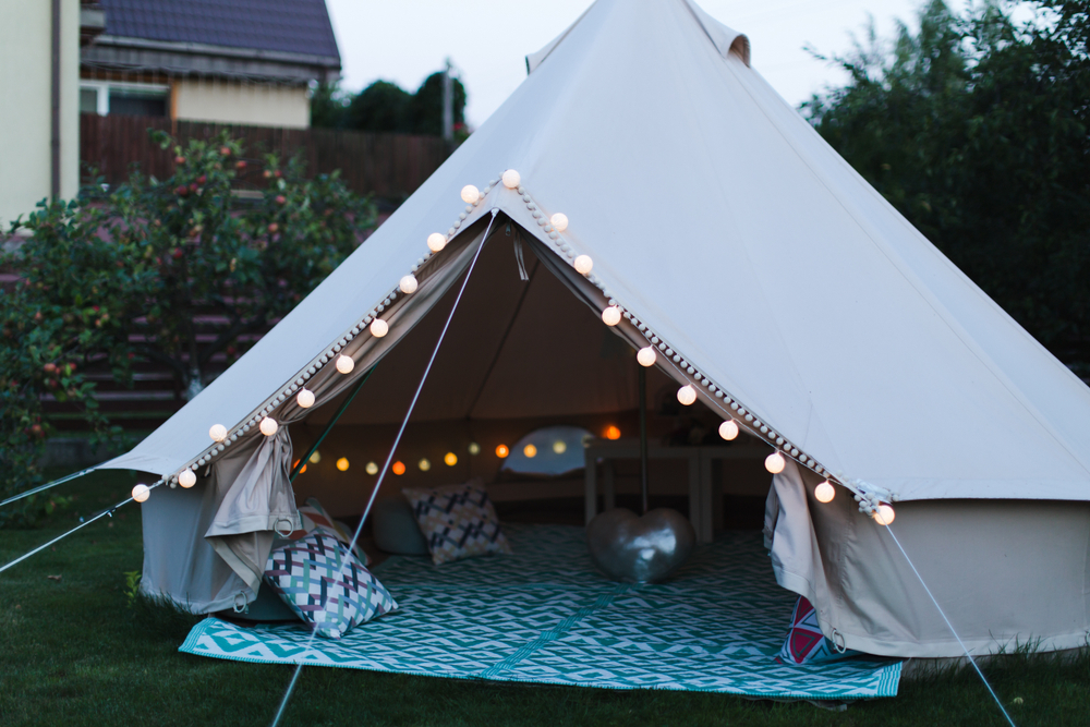 a canvas bell tent with string lights and cushions inside