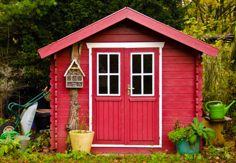 a bright red shed with a white trim
