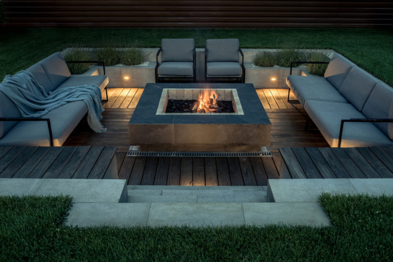 a sleek square fire pit in a luxurious outdoor conversation pit
