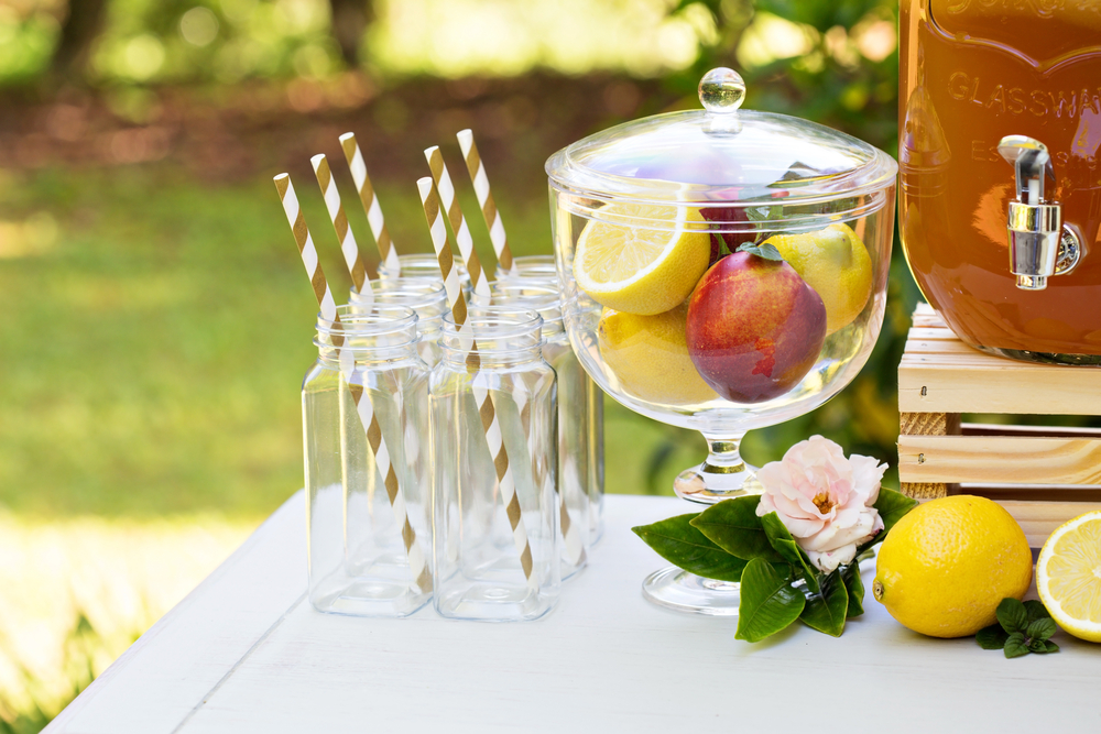 garden party refreshments table with a bowl of fresh fruit and empty glasses