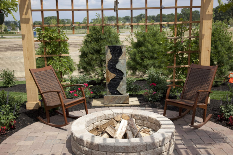 a circular stone fire pit with a pergola, two patio chairs and a vertical fountain