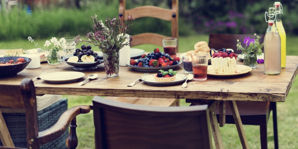 a garden party table laid out with fresh fruit desserts