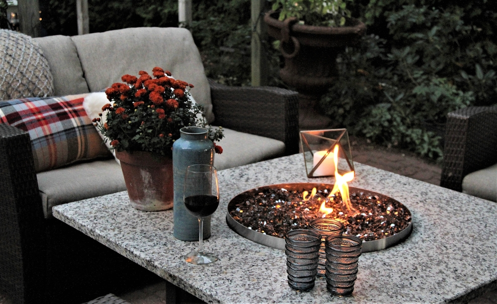 a small round fire pit in a stone topped coffee table