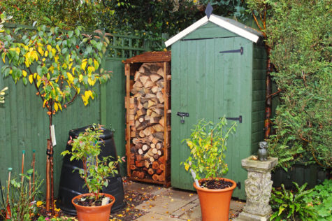 a green shed with log storage in the corner of a garden