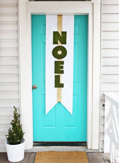 """A bright blue door with a DIY """"noel"""" sign hanging vertically"""