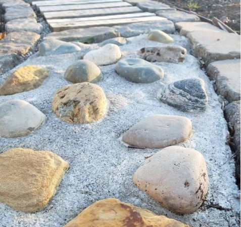 a concrete path with rocks embedded to create an uneven surface