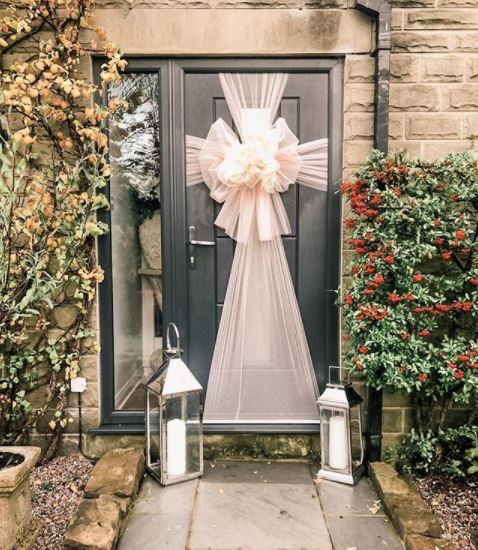 A dark grey door with a shimmery cream bow wrapped around it, like a gift
