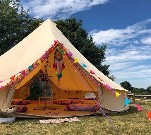 a large open bell tent with rainbow bunting and comfy mattresses with patterned blankets