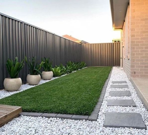a long narrow garden with grey fencing, stepping stones and crisp edging around the lawn