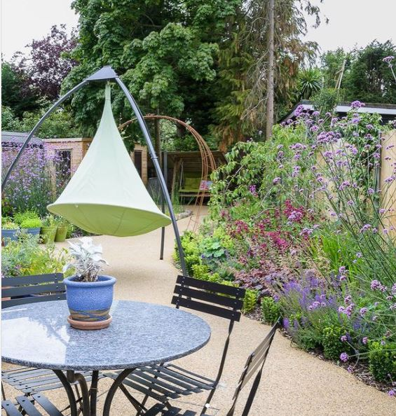 a garden with lots of brightly coloured flowers, a gravel path and a swing seat