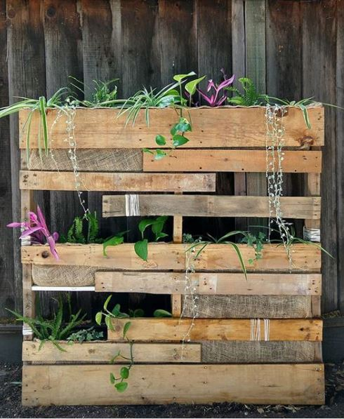 a pallet that's been made into a fence that can hold plants