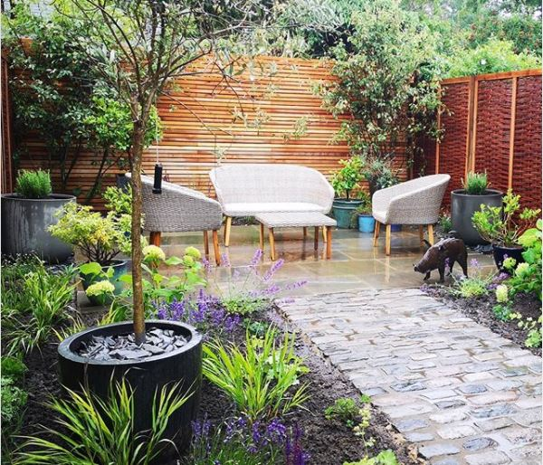 a patio at the far end of a garden with lots of practical pots
