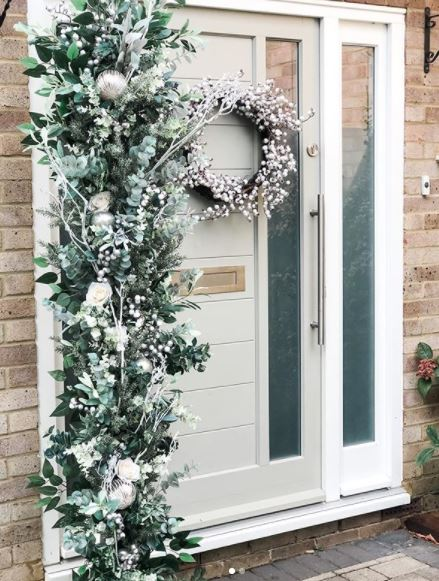 a bushy festive wreath, hanging vertically next to a front door