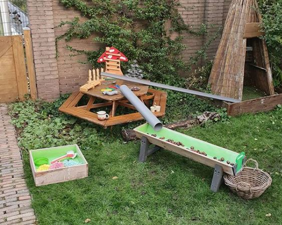 kids garden play area ideas using angled tubes with balls to play with gravity