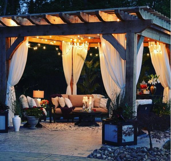 a gazebo with curtains covering comfy outdoor seating with cushions and candles
