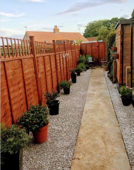 a very long, narrow garden with an off centre path that makes the paving on one side look wider