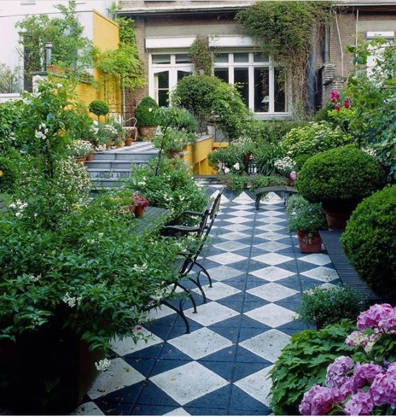 a cottage style garden with checkered paving and steps leading to higher and lower levels