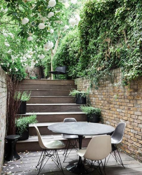 garden steps leading down to a patio area with a dining table enclosed in greenery